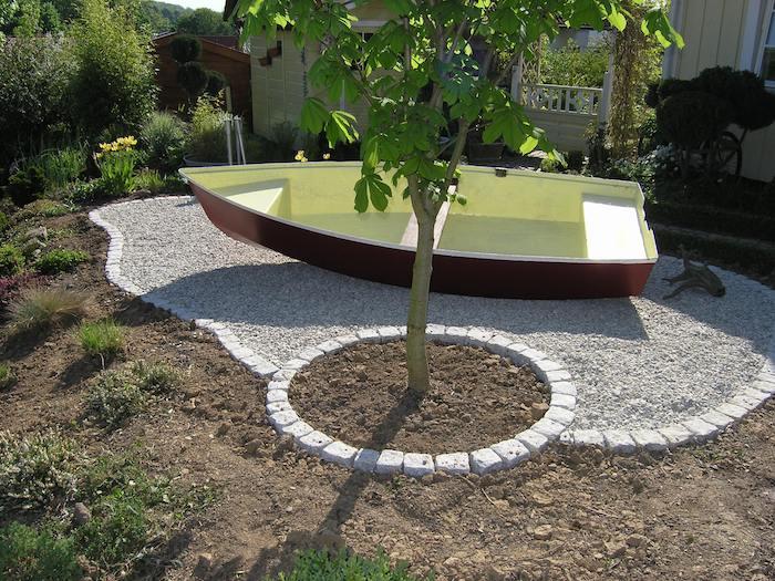 idee deco jardin, technique de jardinage en formes géométriques, petit jardin entouré de pierres avec arbre jeune