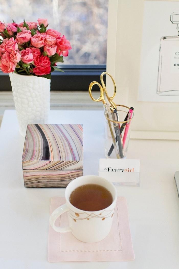 bureau avec plan de travail, bouquet de roses rouges dans vase blanche à motifs galets