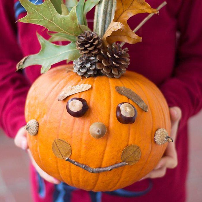 citrouille avec visage de marons, glands, brindille, feuilles mortes, des pommes de pin et feuilles mortes en top, bricolage automne, activités manuelles maternelle halloween