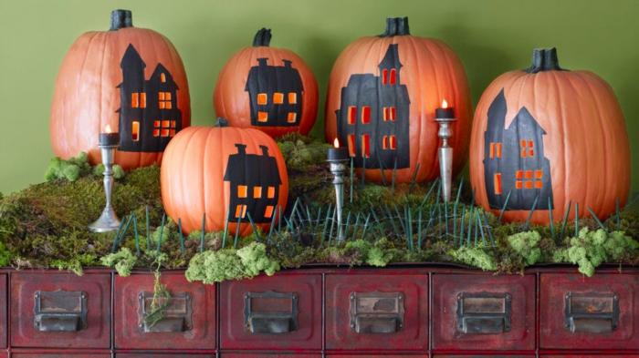 activité manuelle halloween avec des citrouilles et maisons silhouettes noires dessinées dessus et petit fenêtres ouvertures, lanterne halloween