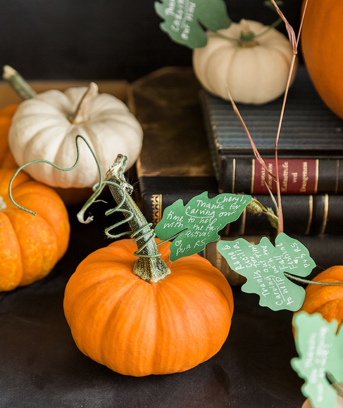 deco halloween a faire soi meme simple avec des citrouille blanche et orange, vieux bouquins, feuilles en papier vert avec des messages
