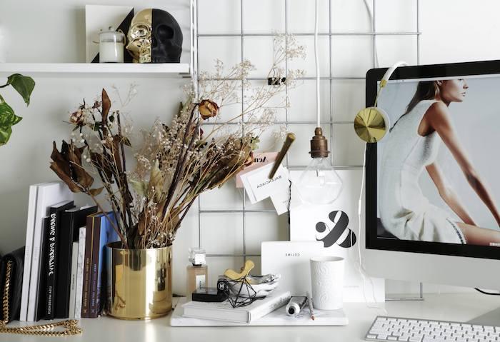 materiel de bureau, vase diy peinte en nuance dorée, collection de livres et magazines, tasse de café blanche