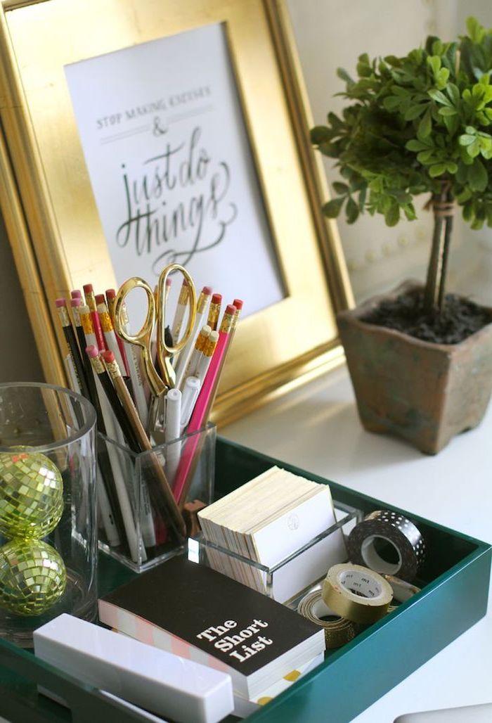 amenagement bureau, petite fleur verte dans pot de terre cuite, cadre photo doré avec poster lettres inspirantes