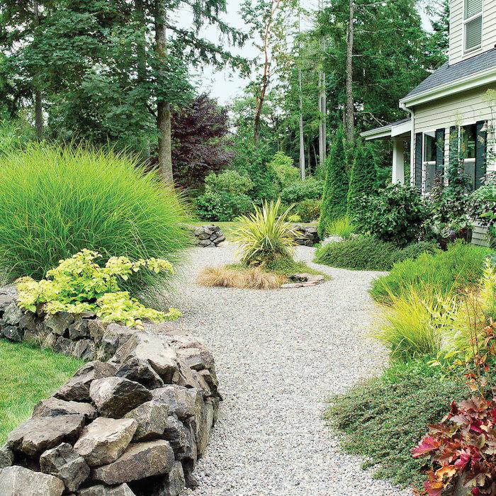 decoration exterieur, jardinage avec cailloux et plantes vertes, façade de maison en bois avec colonnes vertes