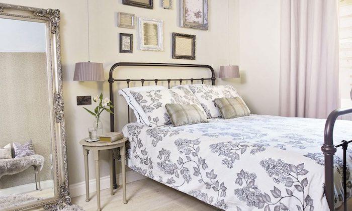 chambre beige avec deco murale, miroir baroque design, lit metallique, parquet bois clair, linge de lit gris et blanc, deco murale de cadres
