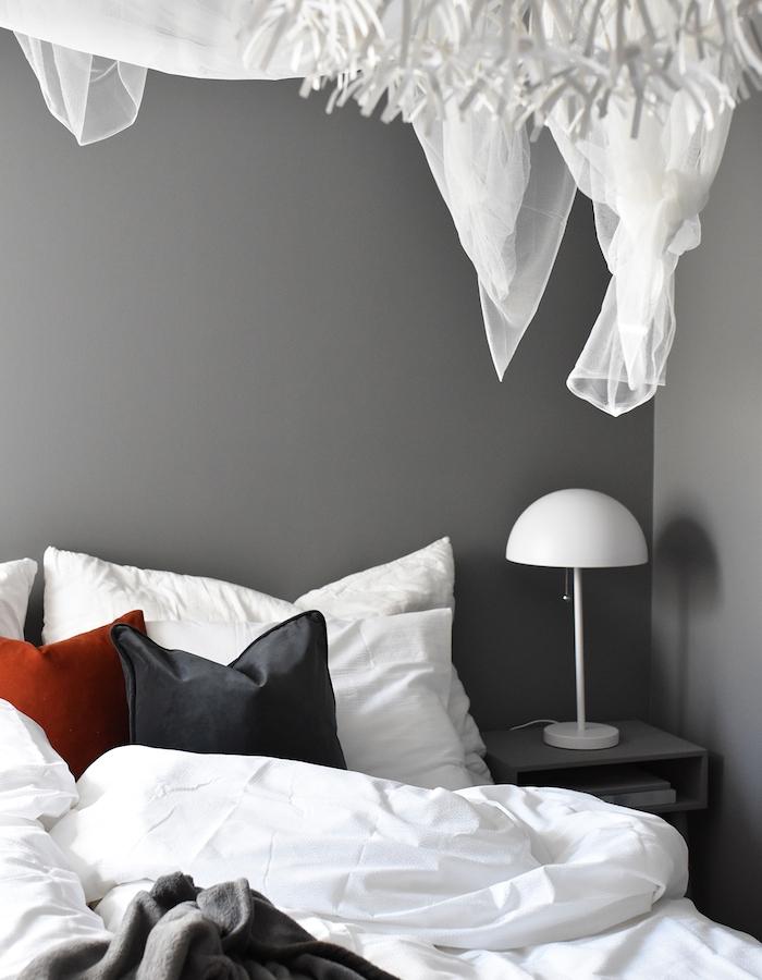 deco chambre parentale avec murs couleur grise et linge de lit gris, blanc et rouge, lampe de nuit design simple