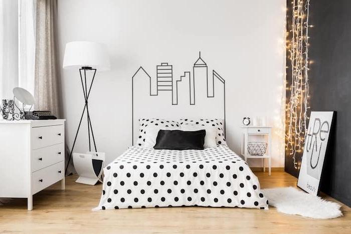 modele de chambre gris et blanc, dessin graphique sur un mur, linge de lit noir et blanc, commode blanche, parquet clair, guirlande lumineuse, tendance hygge