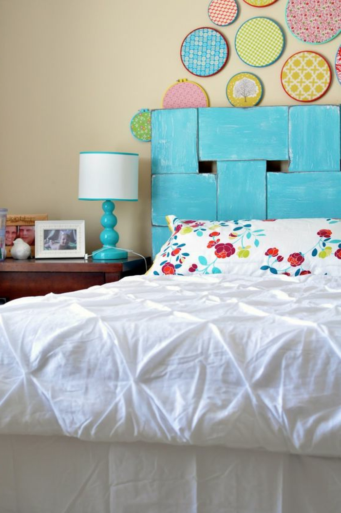 déco chambre adulte avec tete de lit en bleu azur et des panneau décoratifs en forme ronde avec des motifs et des couleurs différents