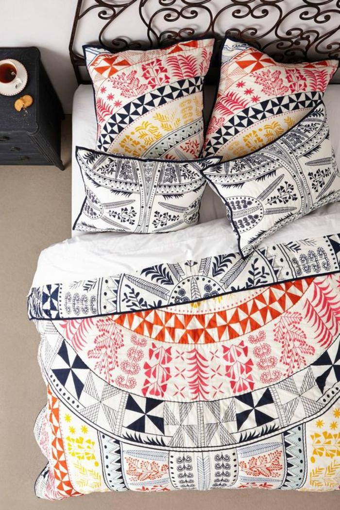 idee deco chambre décoration chambre adulte lit de métal avec tete de lit aux arabesques vintage et couverture et coussins aux motifs graphiques et en couleurs rouge orange noir et blanc