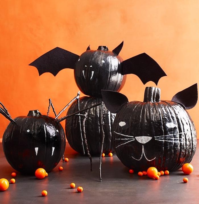 citrouilles repeintes en noir avec des visages dessins blanc, chat, chauve souris, vampire, decoration originale