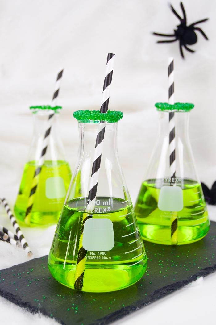un cocktail halloween alcoolique présenté façon laboratoire à base de liqueur midori