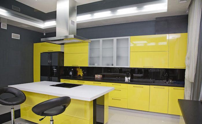 meuble bas cuisine, décoration de cuisine en noir et jaune, cuisine avec ilot centrale blanc et jaune avec tabourets de bar noirs