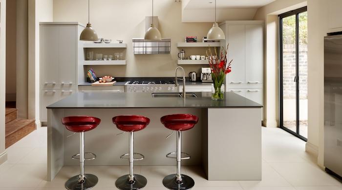 modele de cuisine, ilot central en blanc et noir avec chaises de bar à design rouge, aménagement de cuisine en longueur