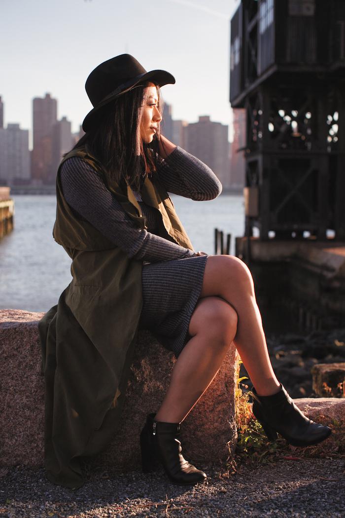 robe bohème chic grise avec manches longues et gilet khaki, bottines en cuir à talons hauts, cheveux noirs avec capeline