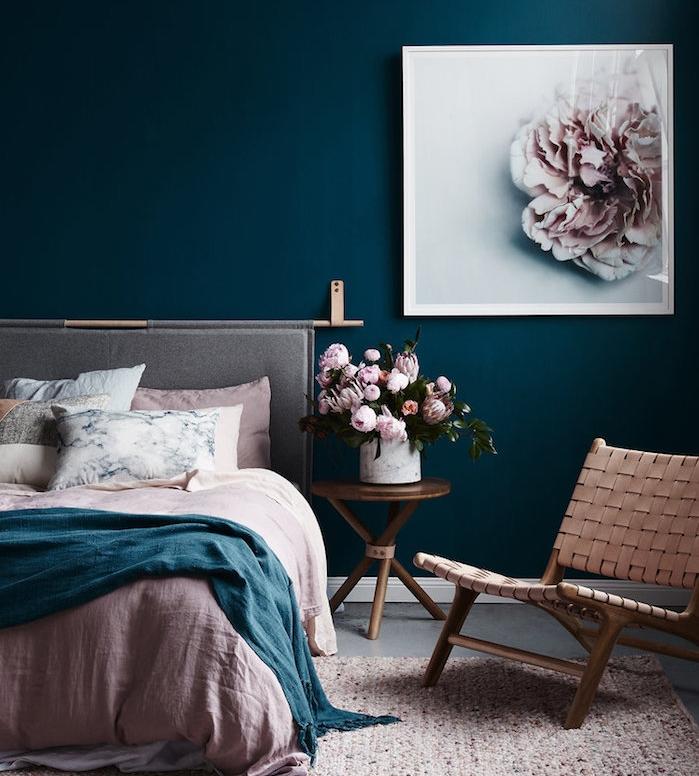 peinture chambre adulte couleur bleu foncé, linge de lit rose, bleu et blanc, fauteuil, table basse en cuivre, avec bouquets de fleurs dans in vase, cadre peinture fleur