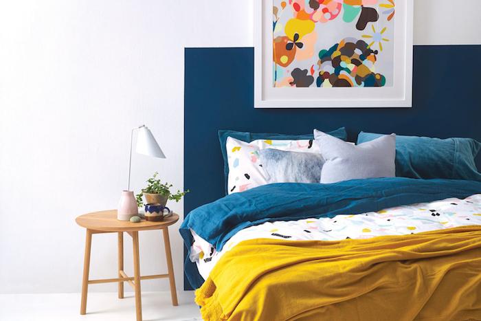 décoration chambre adulte, murs repeint en blanc et tete de lit bleue, table de nuit bois, linge couleur bleue, jaune et blanc, deco cadre peinture abstraite