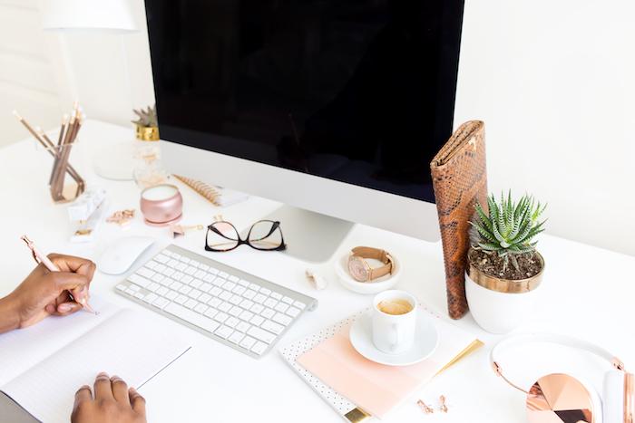 meuble bureau, bougie aromatique en rose pastel, cahier à couverture rose pastel, écouteurs féminins en blanc et cuivre