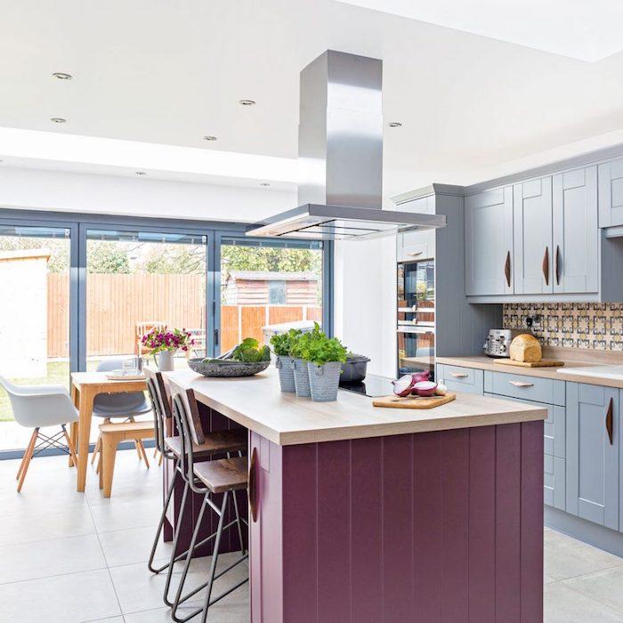 refaire sa cuisine, exemple façade cuisine repeinte en bleu et plan de travail repeint en mauve, coin repas avec table et banc en bois et chaises scandinaves