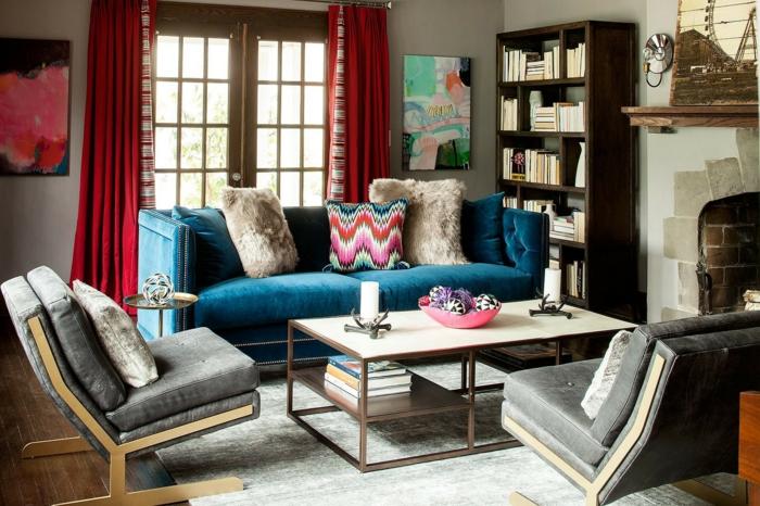 cosy deco, sofa bleu, table en bois et métal, tapis gris, rideaux rouges, étagère bibliothèque