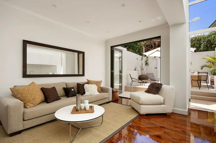 cosy deco, table blanche ronde, sofa beige avec plusieurs coussins, fauteuil blanc, sol en bois, peinture murale blanche