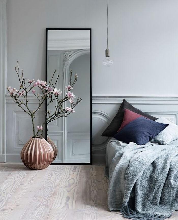 idée déco chambre adulte grise, parquet bois clair, miroir rectangulaire design, linge de lit gris, coussins noir, bordeaux, bleu marine, cerisier dans un vase