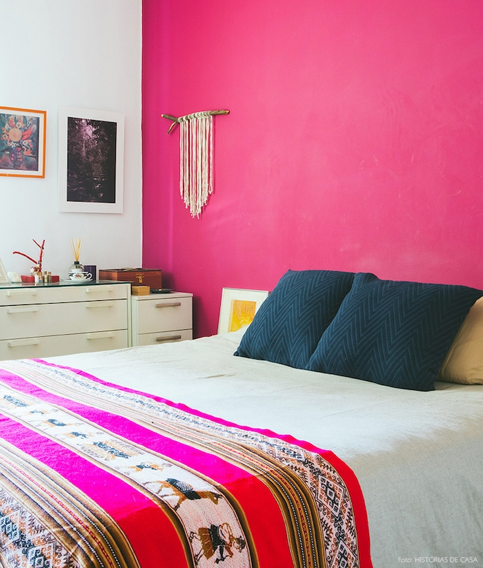 peinture chambre adulte avec mur d accent rose fuchsia, coussins noirs, couverture e lit motifs orientaux, commode blanche, deco murale macramé