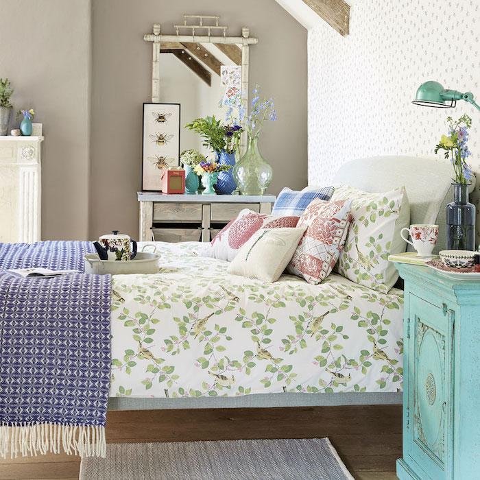 papier peint chambre sur un pan de mur et autres murs couleur grise, linge de lit blanc et vert, couverture bleu et blanc, parquet marron, table de nuit bleu pastel, style campagne chic