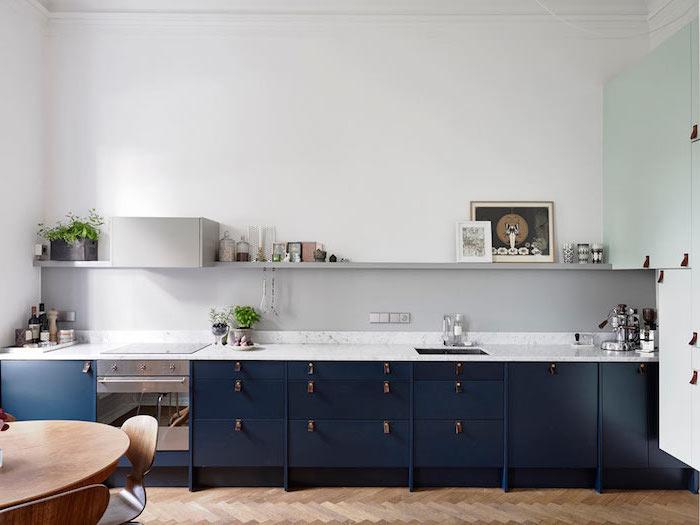 amenagement petite cuisine, meubles de cuisine en bois peints bleu foncé avec comptoir à design marbre blanc