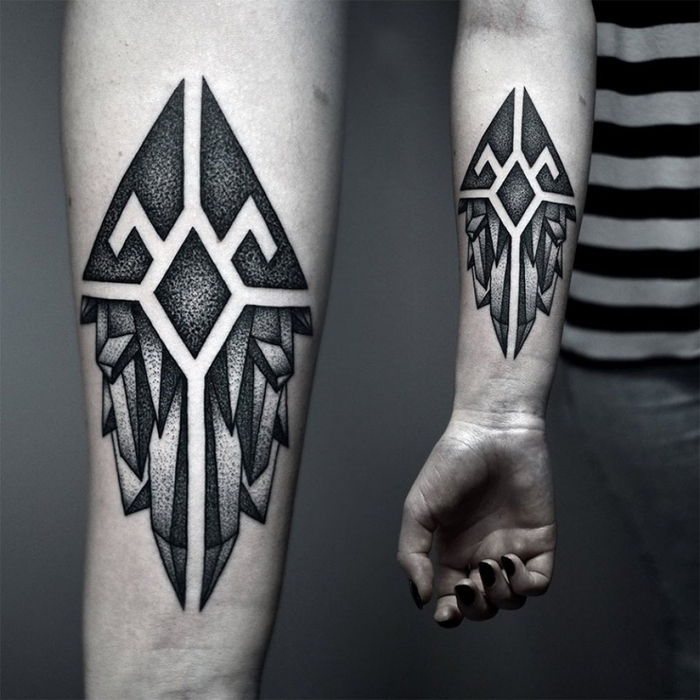 un tatouage pointillé au design masculin représentant un cristal décomposé