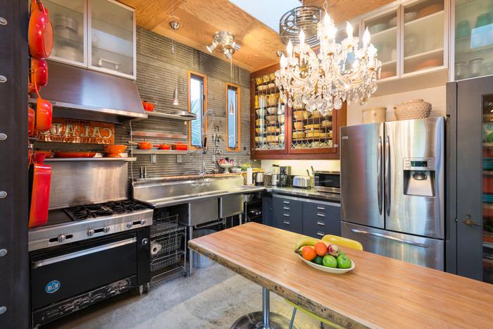 cuisine industrielle en inox et bois avec des armoires à portes vitrées et un lustre en cristal pour un rendu éclectique