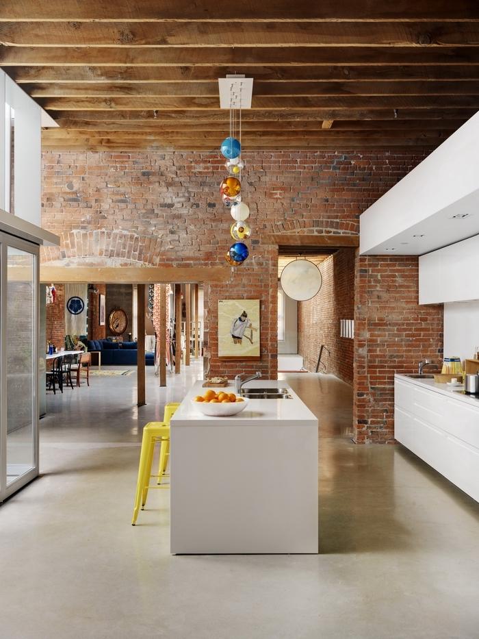 une cuisine esprit loft industriel associant des murs en briques et un design blanc aux lignes épurées