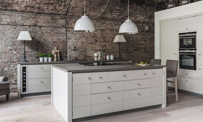 une cuisine industrielle au design moderne jouant sur le contraste du mur en briques et les meubles de cuisine gris mat