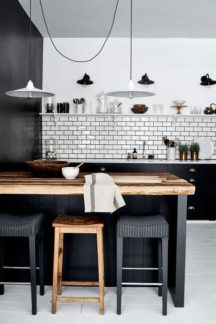cuisine élégante en noir et blanc avec une crédence en briques métro associant une ambiance deco industrielle au chic scandinave