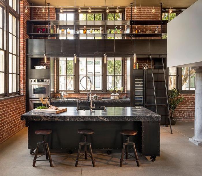 cuisine ouverte de style loft industriel associant briques, acier noir marbre
