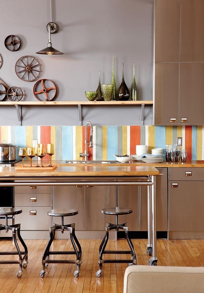 crédence colorée en contraste avec l'ambiance usine crée par les meubles industriels en inox et les objets déco récup