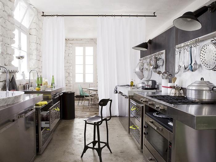 aménagement fonctionnel d une petite cuisine en inox délimitée grâce à un simple rideau