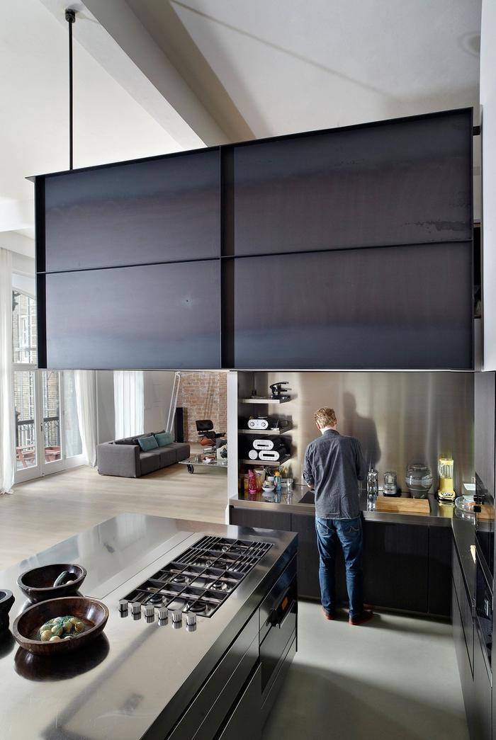 une cuisine industrielle spacieuse au design moderne avec îlot central en inox et une construction en métal suspendue
