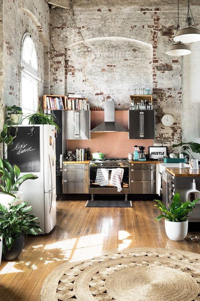 les meubles industriels en inox et les murs en briques confère une ambiance atelier à cette cuisine de style industriel