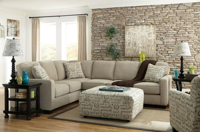 déco salon cocooning, tapis beige, mur en pierre apparente, deux lampes de sol à abat-jour et table de chevet en bois