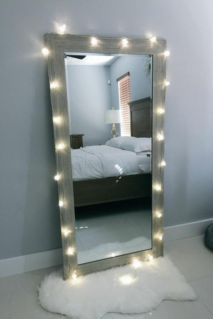 deco chambre adulte avec grand miroir entouré d' une guirlande aux ampoules lumineuses et posé sur un petit tapis blac en fausse fourrure