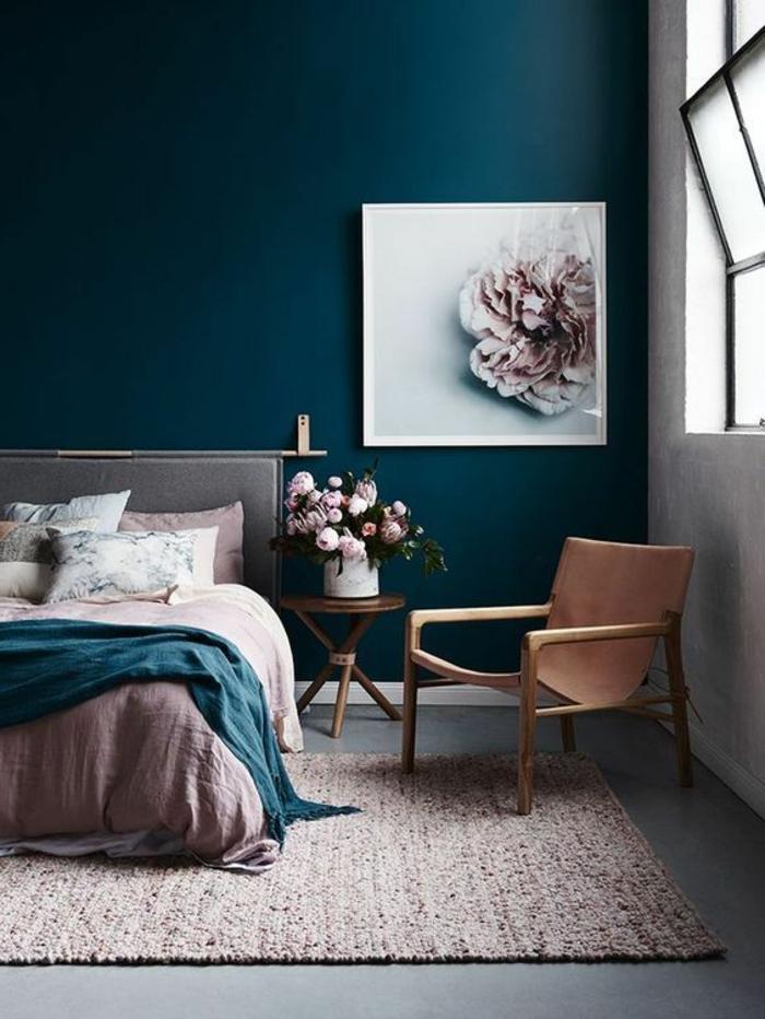 peinture chambre adulte avec mur en bleu pétrole et grand tableau avec une fleur au cadre blanc avec tapis en rose et petits détails noirs