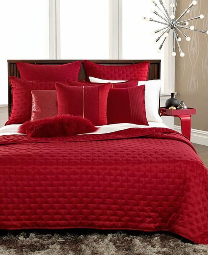 idée déco chambre adulte en rouge rubin avec des grands coussins moelleux et couverture effet matelassée