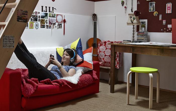 chambre ado fille, canapé rouge couvert de plaid moelleux rouge, murs blancs décorés de cadres photos