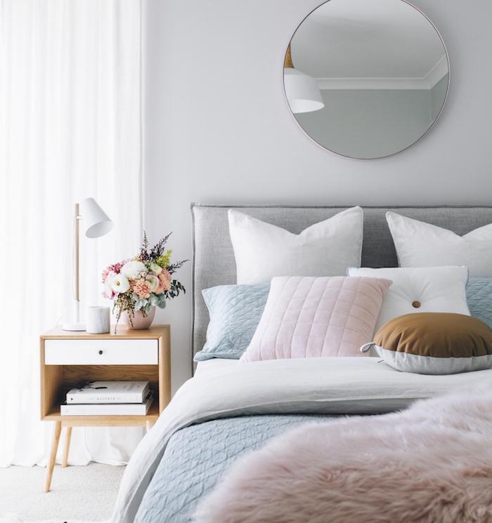 déco chambre cocooning en tons pastel, linge de lit gris, blanc et rose poudré, table, meuble de nuit bois, bouquet de fleurs fraiches, miroir rond