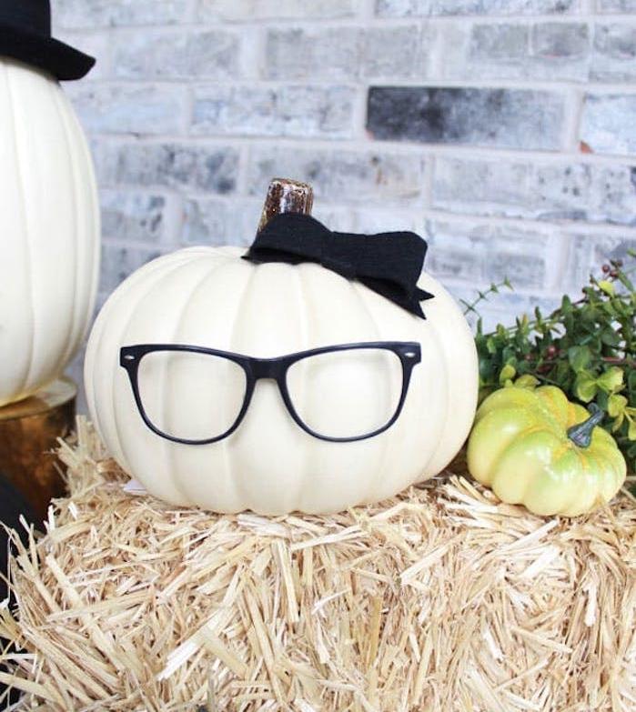 décoration halloween a fabriquer,. une citrouille au noeud noir et des lunettes sur une botte de paille