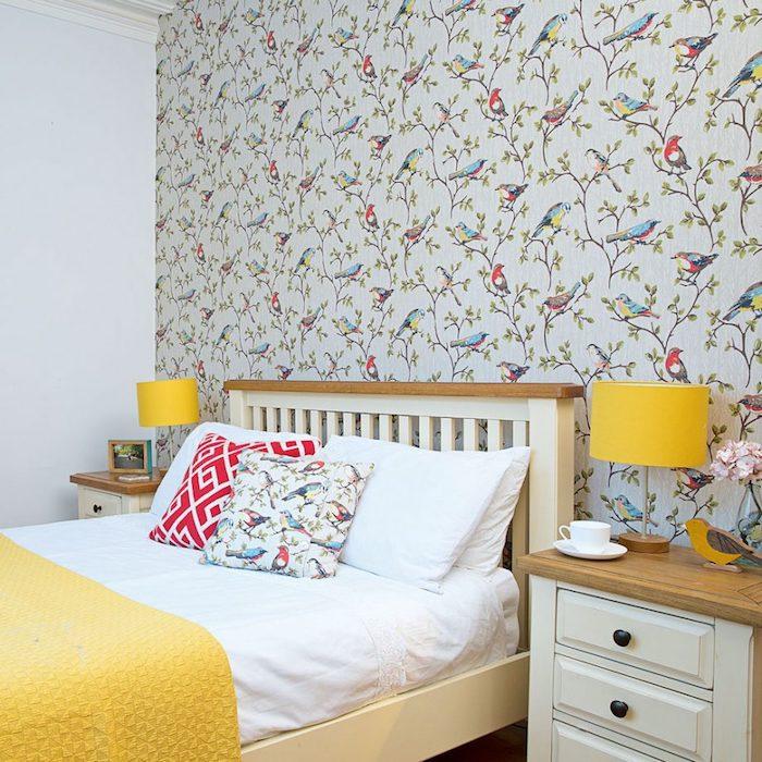 deco chambre adulte avec tapisserie murale motif chinoiserie, branches arbre et oiseaux colorés, lit bois, couverture jaune et table de nuit bois