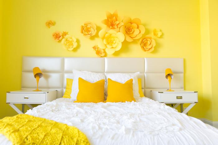 couleur chambre adulte jaune, linge de lit blanc et jaune, deco murale de fleurs en papier, table de nuit blacnhe