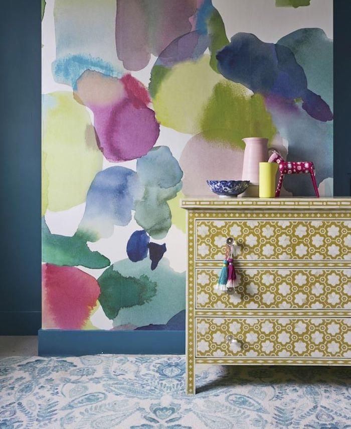 deco chambre adulte avec revetement mural taches aquarelle, imprimé abstrait, commode jaune à fleurs blanches
