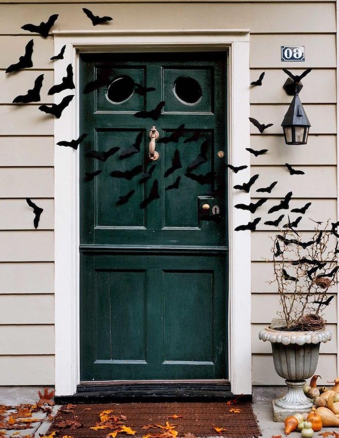 décoration halloween a fabriquer pour la porte entrée, silhouettes de chauve souris en papier, feuilles mortes et citrouilles miniatures, decor macabre