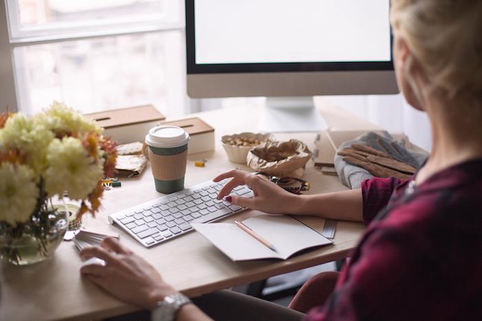 bureau avec plan de travail, bouquet de fleurs jaunes et orange, boîte en marron et blanc, paire de lunettes de vue marron et or